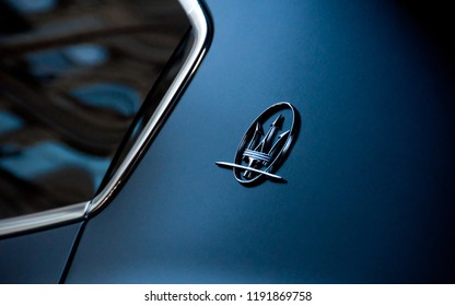 Rome, Italy - January 1, 2018: Maserati car logo on a dark metallic blue car in Rome, Italy. Space for text.