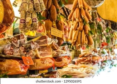 ROME, ITALY - JANUARY 2, 2019: light is enlightening  hanged salami for sale in gourmet shop in Italy