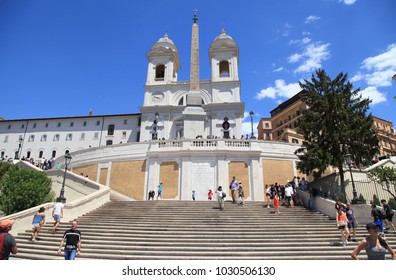 ROME, ITALY - JULY 16, 2017: Tourists on the Spanish Steps with The church of Trinita dei Monti in Piazza di Spagna, Rome, Italy