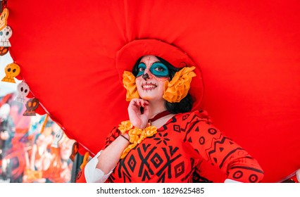 Rome, Italy July 2019. Cosplay event, beautiful young woman dressed as folkloristic character from mexican lore, dead witch in red dress, skelethon face, halloween theme, big red sobrero hat