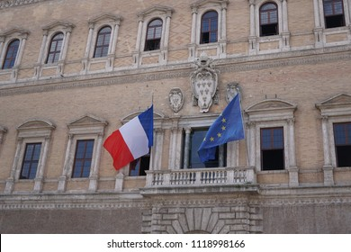 Rome, Italy - June 11, 2018: French and European Union flags fluttering outside Palazzo Farnese, the French Embassy in Rome. The coat of arms of Farnese Pope Paul III is recognizable