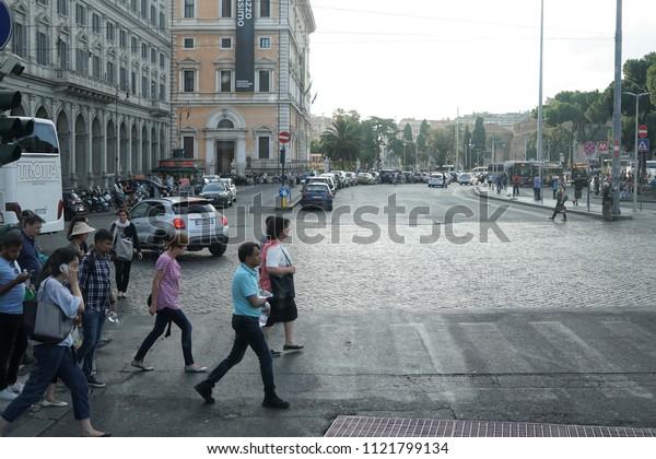 Rome, Italy - June 12, 2018: People walking across a pedestrian pedestrian crosswalk in the city center