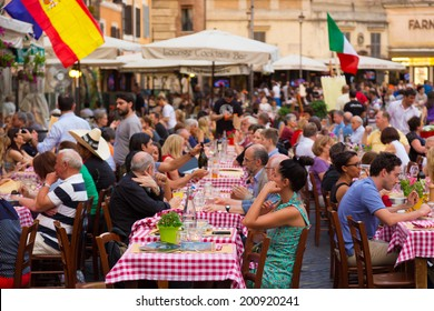 ROME, ITALY - JUNE 13 2014: People having aperitif which in Italy traditionally includes free all you can eat buffet of pizzas and pastas, on JUNE 13 2014 on Piazza Campo De Fiori in Rome in Italy.