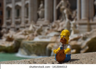 Rome, Italy - June 13, 2018: Homer Simpson Lego Minifigure at the Trevi Fountain with a coin - Image