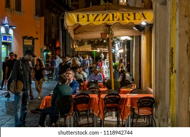 Rome, Italy - June 4, 2018: People dine and mingle at a sidewalk pizzeria at night on a busy street in Rome.