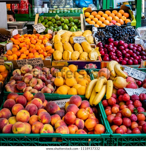Rome, Italy - June 4, 2018; A colorful display of fruit are for sale, including peaches, plumbs, bananas, lemons and limes, at an outdoor stand in Rome.