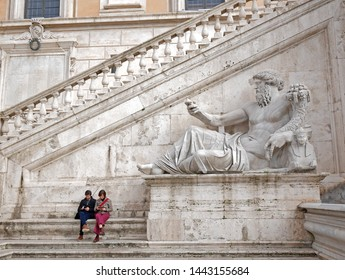 Rome, Italy - March 17, 2019: A man and woman check their phones in a public square. Taken in Italy, and suitable to illustrate modern lives, social media, distractions, or relaxing.