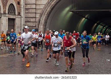 Rome, Italy - March 23, 2014:  Rome Marathon. The participants in the Rome Marathon make their way to the finish line, visibly tired from the 40 km race.