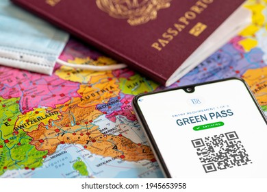 Rome, Italy - March 29 2021: Green or Covid Pass. EU Digital certificate Covid-19. Covid or Coronavirus vaccine certificate, passport app with QR code, passport, mask and map of Europe