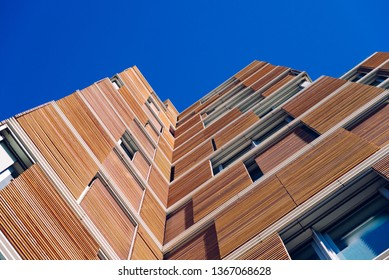 Rome, Italy - March 8, 2019:  View from the floor of the facade of a modern building clad in ecological wood over clean blue sky, concept of sustainable construction background, copy space.