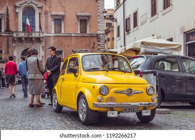 Rome, Italy - May 1, 2017: Small old yellow Fiat parked on a city square. Beautiful bright shiny Fiat 500 standing among people, buildings. A young priest talking with women on the background.