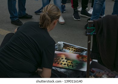 Rome, Italy - May 1, 2019: A back view of a female street artist drawing a picture of a Coloseum on white piece of paper with colorful spray in front of tourists