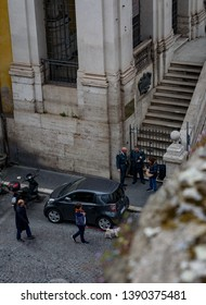 Rome, Italy -May 1 2019: Civil service workers talking in the street and people walking by the parked cars