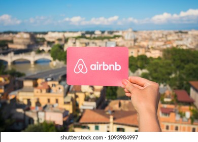 Rome, Italy - May 13, 2018: Person holding Airbnb logo in hand with city in background.