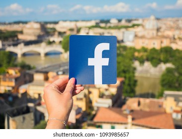 Rome, Italy - May 13, 2018: Person holding Facebook logo in hand with city in background.