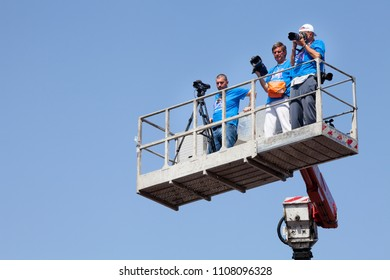 ROME, ITALY. May 17, 2015: Sport photographers reporters and camera operators on an elevated platform during a foot race in Rome in Italy. Race for the cure, run for charity against breast cancer.