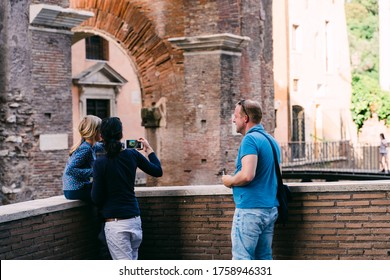 Rome, Italy - May 1o, 2020: A young family of tourists takes a photo of the ancient Portico d'Ottavia in the Jewish Quarter