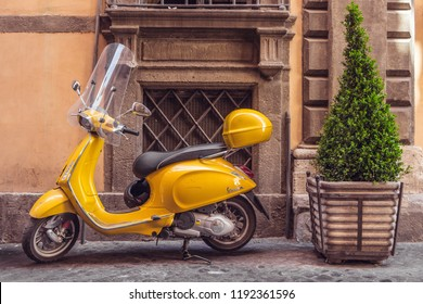 Rome, Italy - May 2, 2017: Small old yellow scooter Vespa parked on a narrow cobblestoned street of old town. Typical street scene in Rome with a scooter outside. Window, wall, tree on the background.