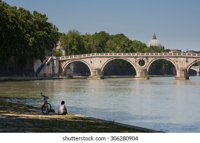 ROME, ITALY - MAY, 2015: A woman resting near her bike by the river Tiber in front of Ponte Sisto and Saint Peter's Dome.