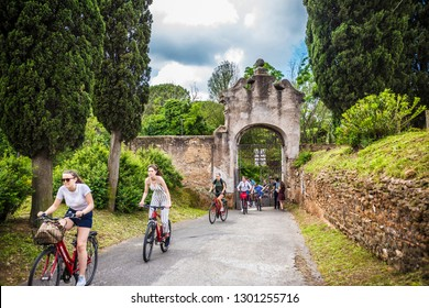 ROME, ITALY - May 2018: Cycling people at the entrance gate to the Catacombe di San Callisto cave historical town in Rome, Italy
