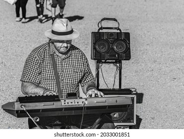 Rome, Italy, May 2018, a man strumming his table organ to earn something extra