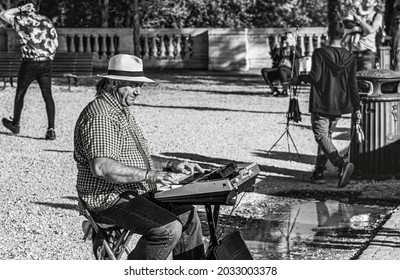 Rome, Italy, May 2018, the same man but taken from a different angle strumming his table organ to earn a little extra