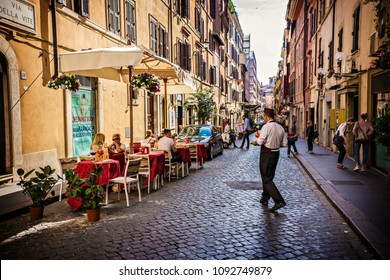ROME, ITALY - May 2018: Street restaurant in Rome, Italy. Waiter serving cocktails , aperol spritz at outdoors cafe in Rome, Italy
