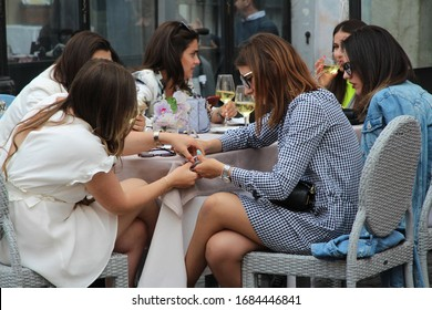 Rome, Italy, May 2019: Tourists walk near the Pantheon, a group of young girls at a table in a street cafe chatting and having lunch