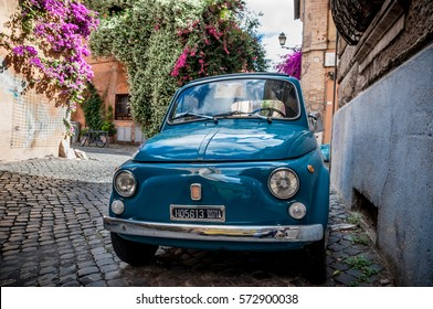 Rome, Italy - May 27, 2014: Old Fiat Nuova 500 city car parked near the wall with beautiful flowers on the background