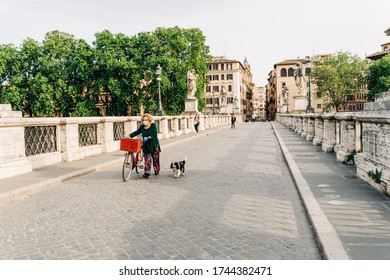 Rome, Italy - May 8 2020: elderly woman with a face mask walking a dog and bicycle along Ponte Sant'Angelo during COVID-19 lockdown