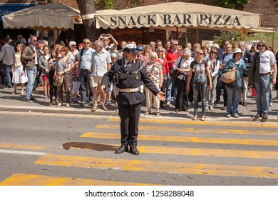 Rome, Italy, May 9, 2013:Uniformed Police woman on traffic duty at a pedestrian crossing near the Coloseum, Rome