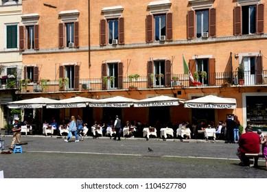 Rome, Italy - May 9, 2018: people eat at restaurant with outdoor tables in the historic Piazza Navona.