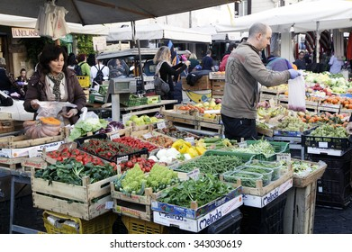 ROME, ITALY - NOVEMBER 07 2015: Sellers behind their stall while take his goods displayed on stall at outdoor market in Rome, Italy
