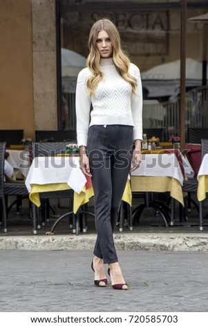 3babc6e24a667 Rome, Italy - November 17, 2016: Blonde woman in urban background.  Beautiful young girl wearing elegant sweater and trousers poses in the  street.