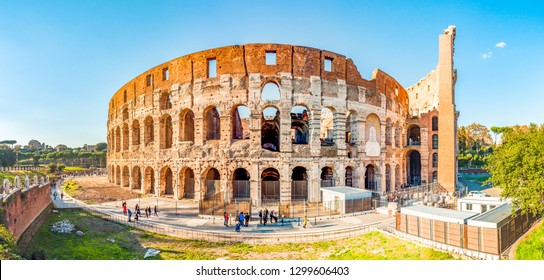 Rome, Italy - November 17, 2018: Wide outside panorama of Colosseum or Coliseum, known as the Flavian Amphitheatre, is an oval amphitheatre in the center of the city of Rome full of people
