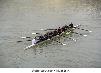 Rome, Italy - November 19, 2016: Males rowing team in race on the Tiber River. Teamwork concept.