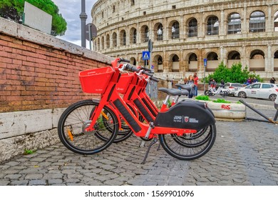 Rome, Italy - November 20 2019: Red Uber Jump pedal-assist bikes parked. Dockless Electric Bicycle sharing system rentals with basket on a sidewalk at Colosseum area in the Roman capital.