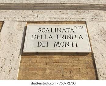 Rome, Italy - November 8, 2017: Scalinata della Trinità dei Monti (French: La Trinité-des-Monts) street sign on wall. The Spanish Steps lead down to the Piazza di Spagna