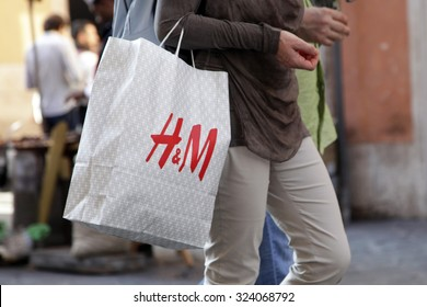ROME, ITALY - OCTOBER 03 2015: People walk with their H&M shopping bag on Via Ripetta, main shopping street in the center of Rome, Italy