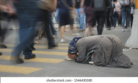 ROME, ITALY - OCTOBER 06, 2018: Indifferent people pass beside a homeless beggar woman squatting down the street waiting for mercy, conceptual scene of the modern social, economico-political crisis