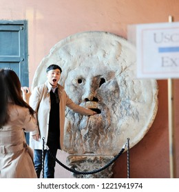 Rome, Italy – October 10, 2018: Asian man and woman photograph each other in front of the mouth of truth (Bocca della Verità). Church of Santa Maria in Cosmedin in Rome, Italy