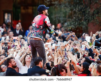 Rome, Italy - October 16, 2016. The Italian singer Jovanotti with his fans on the red carpet of the 11th International Film Festival of Rome. Jovanotti standing among the fans exults and urges crowd.