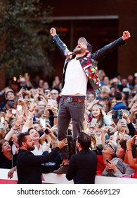 Rome, Italy - October 16, 2016. The Italian singer Jovanotti with his fans on the red carpet of the 11th International Film Festival of Rome. Jovanotti standing among the fans rejoices raising his arm
