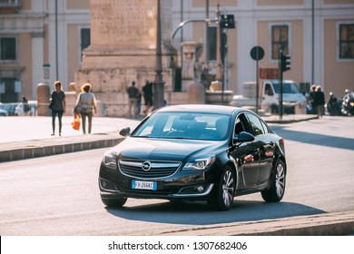 Rome, Italy - October 19, 2018: Black Color Opel Insignia With Face-lift In First Generation Moving At Street. Insignia is a family car engineered and produced by the German car manufacturer Opel