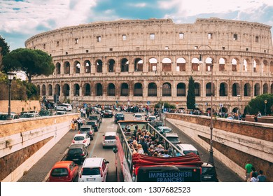 Rome, Italy - October 21, 2018: Colosseum. Red Hop On Hop Off Touristic Bus For Sightseeing In Street Near Flavian Amphitheatre. Famous World UNESCO Landmark. City Sightseeing Tour.