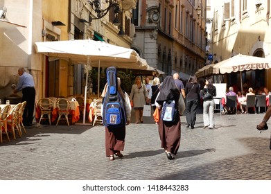 Rome / Italy - October 5, 2009: Two nuns, one with a guitar strapped to her back, walk through the cobblestone streets of Rome.