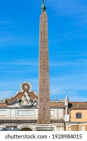 Rome, Italy - October 9, 2020: An Egyptian obelisk ( Flaminio Obelisk) of Ramesses II from Heliopolis with hieroglyphs in the centre of the Piazza del Popolo and Porta del Popolo
