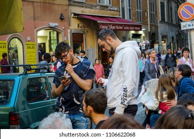 ROME, ITALY - OKTOBER 30, 2016: The crowd gathers in an alleyway leading to the famous 'Fontana di Trevi' as the two young men distracted with their phones remain oblivious.
