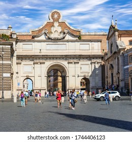 Rome, Italy - Sept 2, 2014: Tourists entering Piazza del Popolo through Porta Popolo on right church of Santa Maria del Popolo. This is the ancient Porta Flaminia of Aurelian Wall.