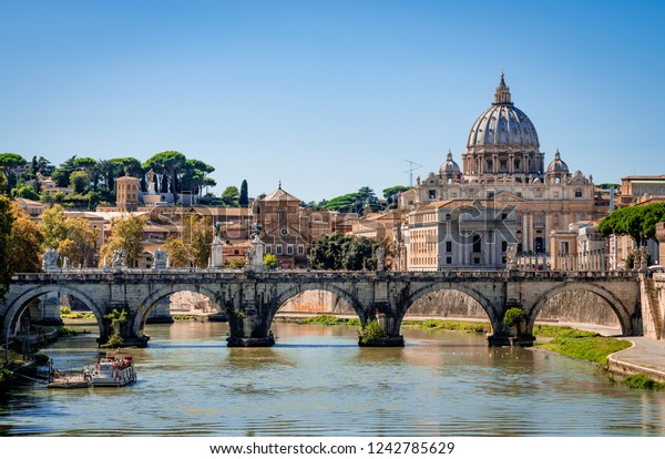 Rome / Italy - September 13 2014: View of Ponte Sant'Angelo (St. Angelo Bridge) that spans river Tiber with the dome of Saint Peter's Basilica in the background.